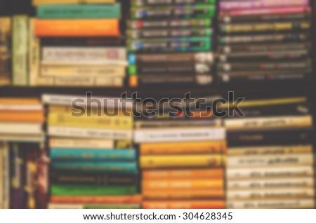 De focused/Blurred image of books on bookshelf. Retro effect. Book background. - stock photo