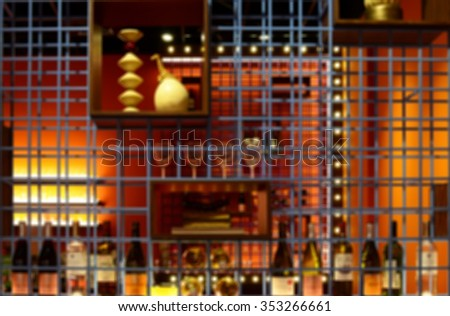 De focused/ Blurred image of  wine bottles and wineglasses on the shelves.