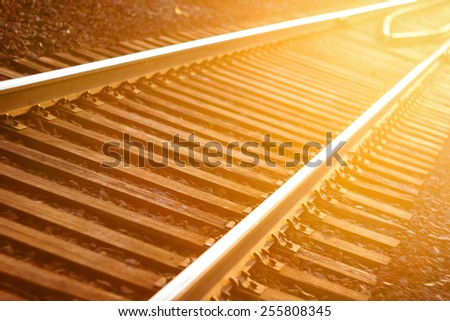 De focused curved railroad tracks in sunset, travel background - stock photo