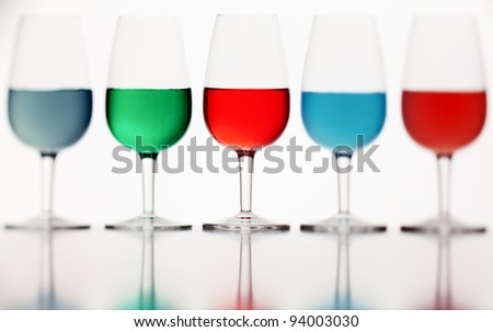 de focused glasses of colored liquid photographed on a white background