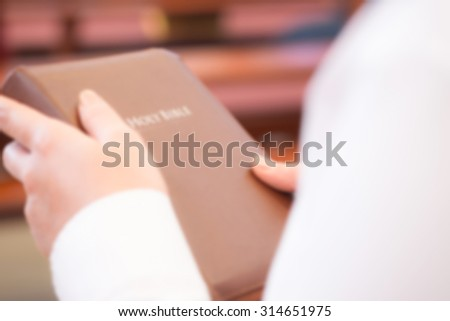 De focused or blurred image for a woman holding holy bible in the church for religion background - stock photo