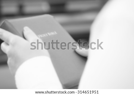De focused or blurred image for a woman holding holy bible in the church for religion background in white and black color tone - stock photo