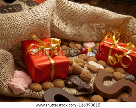De zak van Sinterklaas (St. Nicholas' bag) filled with suikergoed, kruidnoten, letters of chocolate and gifts. All part of the traditional Dutch december holiday 'Sinterklaas'. - stock photo