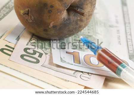 "Dead apple with syringe on dollars - concept ""Narcotic drugs kill"" - stock photo"