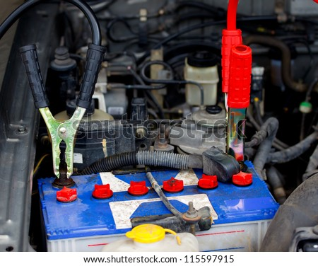 dead battery clamped with battery jumper to recharge the power - stock photo