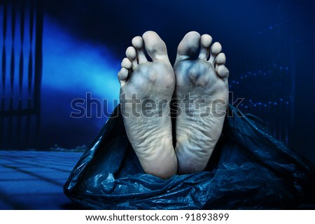 dead body in a plastic bag lying in the street at night - stock photo