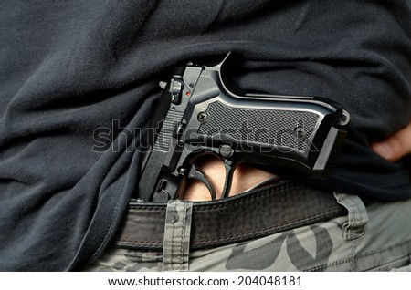 Dead burglar with 9 mm pistol in hand - stock photo
