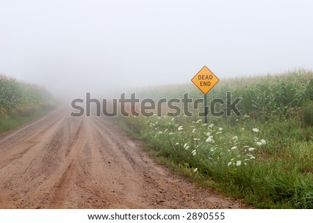 Dead End Road. Foggy morning on an old country dead end road. - stock photo