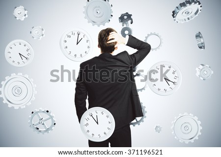 Dead line concept with businessman holding his head and flying watches and gears