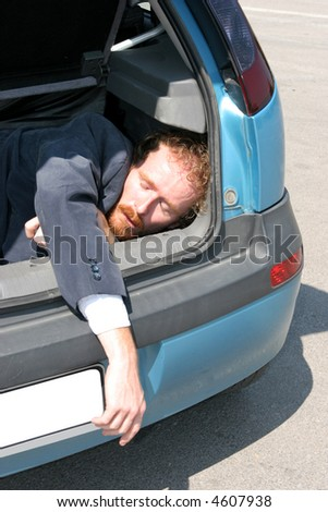 Dead man in car boot - stock photo