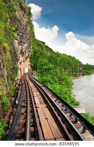 Dead railway beside cliff along Kwai river in Thailand - stock photo