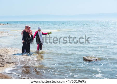 DEAD SEA, JORDAN - AUGUST 12, 2016: two unidentified women walk on the salted coast of the Dead Sea, in Amman Beach. One of them dress the burkini.