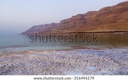 Dead sea landscape with salt structures on the shore and desert mountains in the background - stock photo