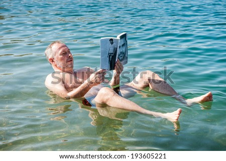 DEAD SEA RESORT, JORDAN - MAY 1, 2014: Unidentified man reads a book laying on the water surface of the Dead Sea. Dead Sea water is used for medical purposes for the people with skin problems