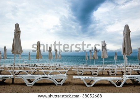 Dead season. Rows of closed umbrellas and deckchairs on the empty beach before a storm. - stock photo