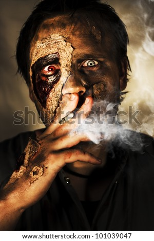 Dead Sexy Male Zombie Smoking On A Cigarette Cancer Stick With A Look Of Bloodshot Horror, Terror And Fear In A Killing Time Conceptual