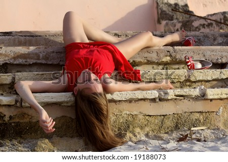 dead woman in red dress on the stairs - stock photo