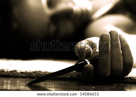 dead woman lying on the floor, knife in the hand - stock photo