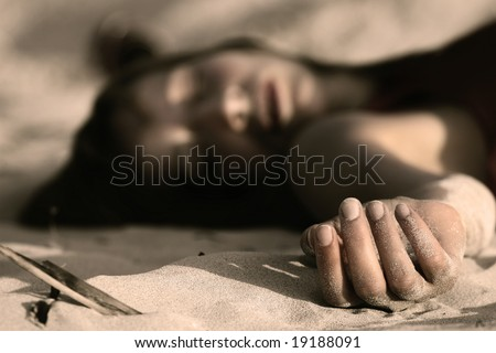 dead woman on the sand - stock photo