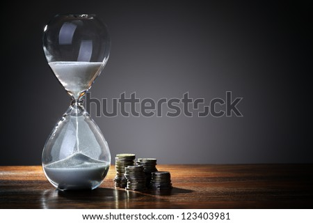 Deadline and time is money concept with hourglass and British coin currency - stock photo