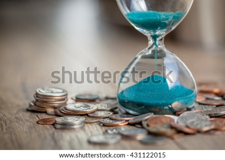 Deadline and time is money concept with hourglass and US coins currency. sandglass - stock photo