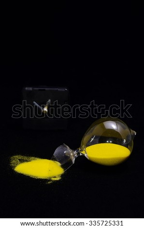 Deadline Concept Broken Hourglass with Yellow Sand on Black Background - stock photo