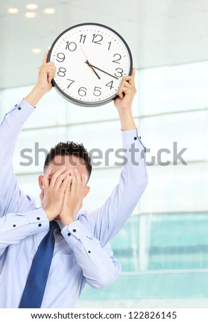 deadline concept of businessman with many hands holding clock and covering face in the office - stock photo