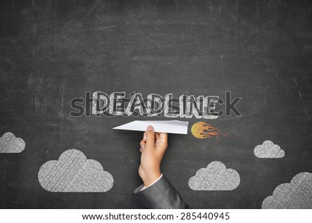 Deadline concept on black blackboard with businessman hand holding paper plane - stock photo