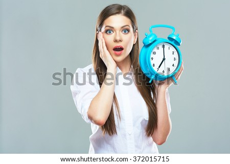 Deadline concept with shocked woman holding  alarm clock. Studio isolated. Business woman white shirt dressed. - stock photo
