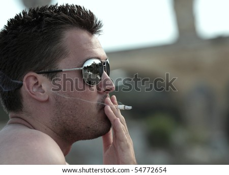 Deadly nasty habit - Male smoker wearing sunglasses smoking a cigarette outdoors - stock photo