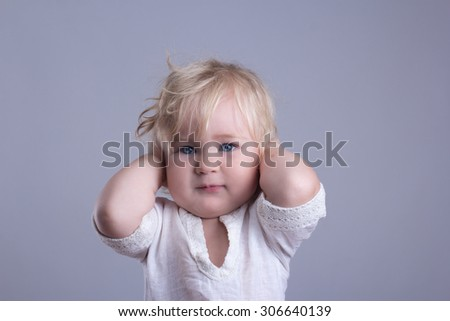 deaf baby blue eyes blonde long hair gray background - stock photo