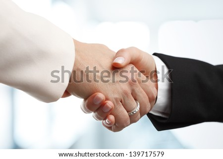 Deal! Close-up of two businesswomen shaking hands against an office backgrounds. Focus on hands - stock photo