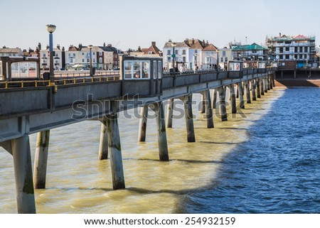 DEAL, UK - FEB 17, 2015: Visitors and locals enjoy Deal Pier which opened on 19th November 1957, it is a grade II listed building, constructed mainly from concrete-clad steel. It is 1026 ft long. - stock photo