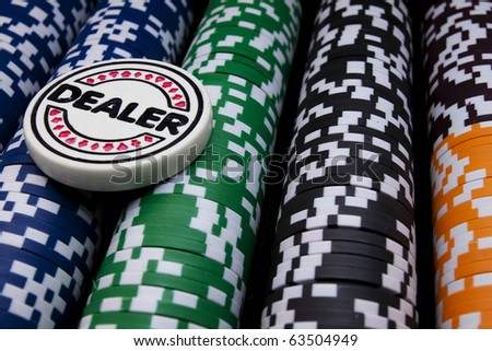 Dealer Button and Chips A poker dealer button sitting on rows of gaming chips. Horizontal. - stock photo