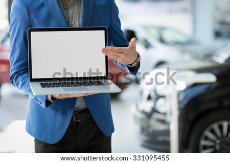 dealer car shows the best offer, pointing in blank screen - stock photo