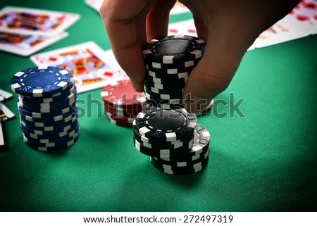 dealer collects poker chips from the table - stock photo