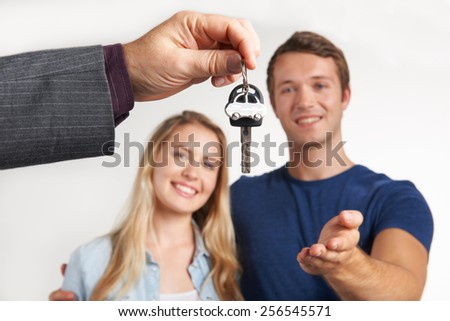Dealer Handing Over Keys For New Car To Young Couple - stock photo