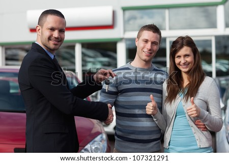 Dealer shaking hand of a man while giving him car keys in a dealership - stock photo