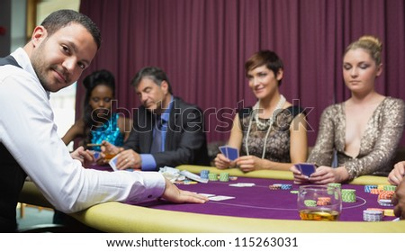 Dealer smiling at poker game in casino - stock photo