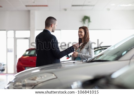 Dealer speaking with a client in a dealership - stock photo