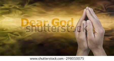 Dear God - Male hands in prayer position on a golden streaming background with the words Dear God to the left and plenty of copy space beneath - stock photo