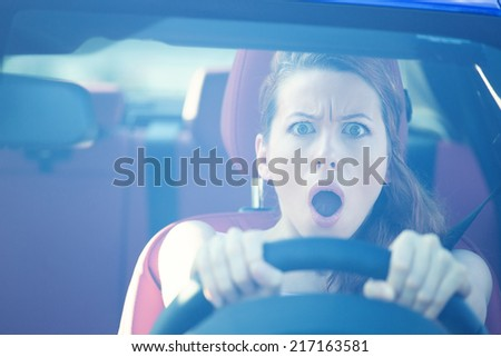 Dear in headlights. Fright face woman driving car, wide open mouth eyes, strongly squeezing wheel, front window view. Negative human face expressions, emotions, reaction. Road trip risk danger concept - stock photo