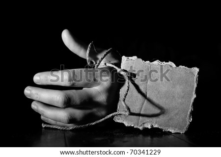 Death concept. Hand of a corpse on a wooden floor with cardboard tag on rope. Black&White, grunge processing image with grain added - stock photo