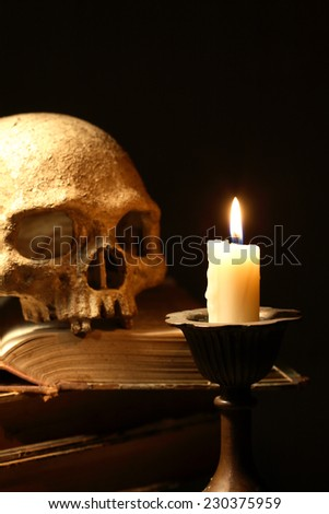 Death concept. Human skull on old books near candle on dark background