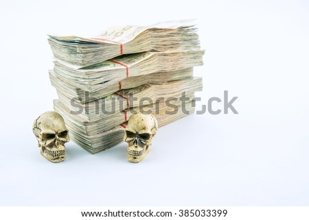 Death for money : 2 skulls with stack of 1000 bath Thai money - BankNotes isolated on white background   - stock photo