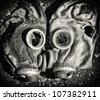 Death kiss. Black and white gas masks with broken glass. Black and white photo. - stock photo