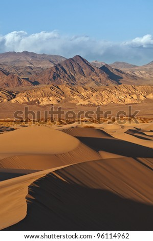 Death Valley. Image of rocky desert in Death Valley National Park with Mesquite Sand Dunes in the foreground. - stock photo