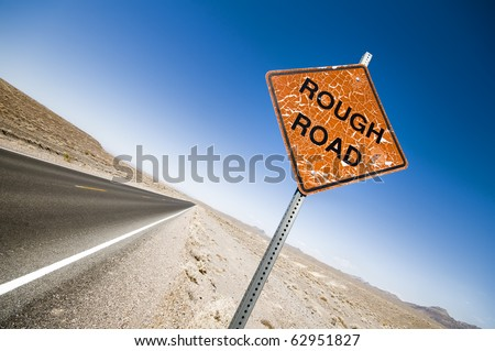 Death Valley Rough Road sign, clear blue sky and an open straight empty road - stock photo