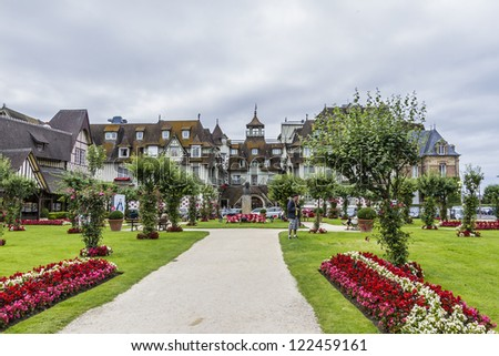 DEAUVILLE - JULY 18: A beautiful park near Normandy Barriere hotel on July 18, 2012, Deauville, France. 5 star hotel has 290 rooms and was constructed in 1913 and is famous for half-timbering decor. - stock photo