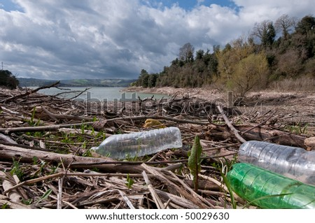 Debris and pollution on lake shore - stock photo